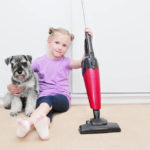 Girl holding dog and a cordless stick vacuum