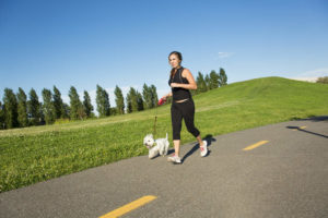 Young woman jogging with her Westie