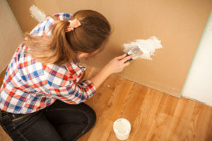 Woman repairing hole in drywall from dog