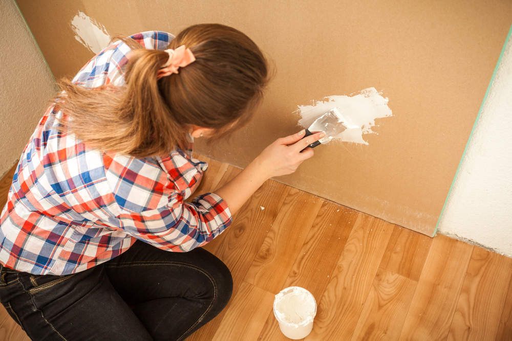 Woman repairing hole in the drywall from the dog